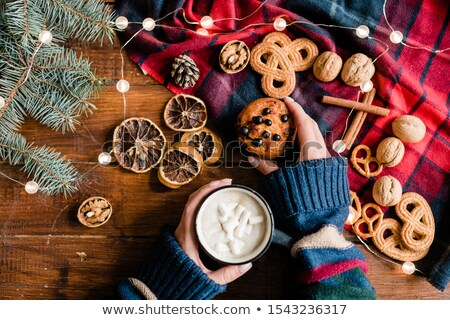 Hand of girl taking homemade cupcake and having hot drink with marshmallows Stock photo © pressmaster
