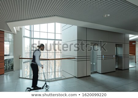 Blurred outline of young businessman moving on scooter in office center Stock photo © pressmaster