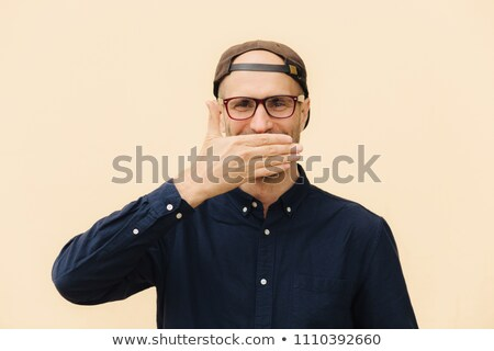 Positive male model covers mouth as giggles at funny joke, wears spectacles, cap and elegant shirt,  Stock photo © vkstudio