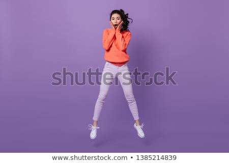 Full length image of asian woman expressing surprise and looking Stock photo © deandrobot