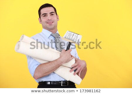 young handsome man carrying rolls of wallpaper against yellow background Stock photo © photography33