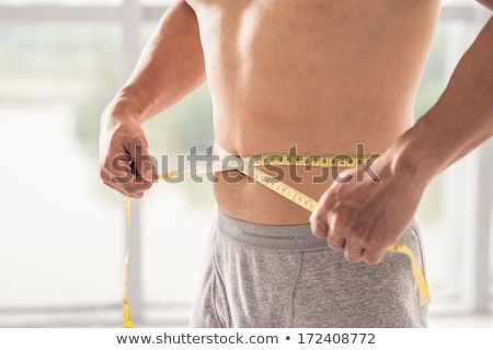 Muscular man measuring waist  Stock photo © tommyandone