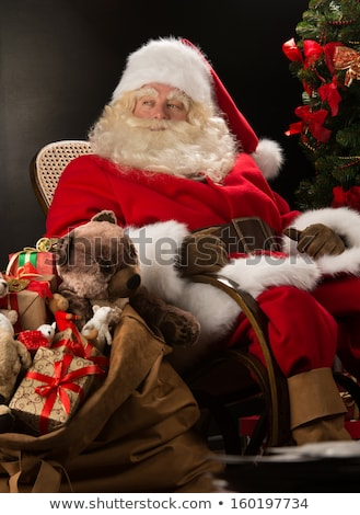 Stockfoto: Santa Claus Sitting In Rocking Chair Near Christmas Tree At Home