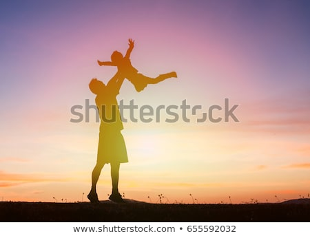 Father and son in the sea silhouetted at sunset Stock photo © smithore