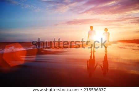 young happy couple kiss on a beach during sunset stock photo © tommyandone