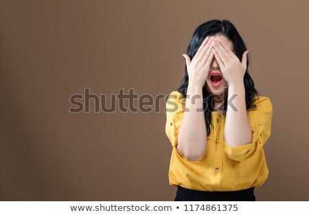 woman covering her eyes with orange stock photo © deandrobot