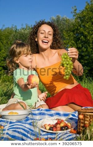 Stock photo: pretty Little Girl and Young Women keeps in hand fruits on picni