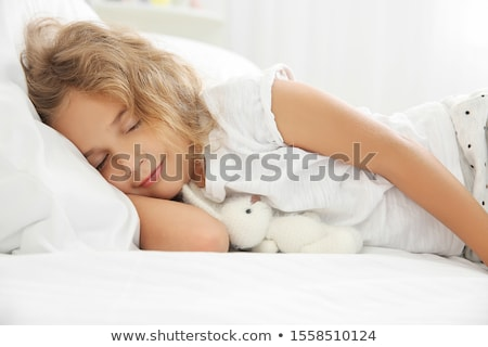 Little girl lying in bed stock photo © deandrobot