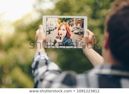 Aranyos fiatal nő tabletta küldés csók táblagép Stock fotó © deandrobot