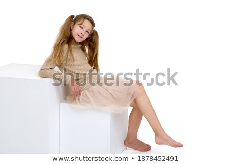 Portrait of model in casual clothes sitting on white cube Stock photo © julenochek