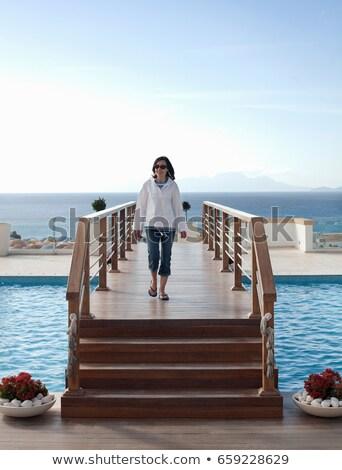 Woman on walkway over swimming pool Stock photo © IS2