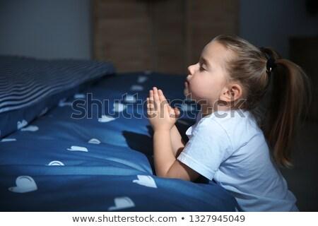 Girl saying bedtime prayers Stock photo © IS2
