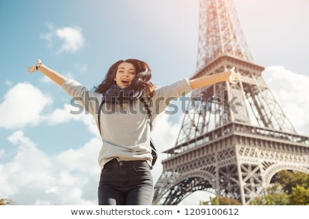Young attractive happy woman jumping for joy against Eiffel Tower in Paris, France Stock photo © artfotodima