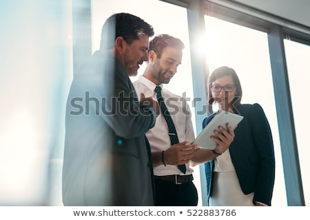smiling businesspeople looking at digital tablet stock photo © kzenon