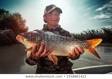 Fisherman holding big fish in hands Stock photo © colematt