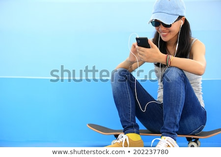 Sports woman in park outdoors listening music with earphones. Stock photo © deandrobot