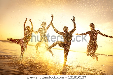 group of young friends enjoying picnic on beach together stock photo © monkey_business