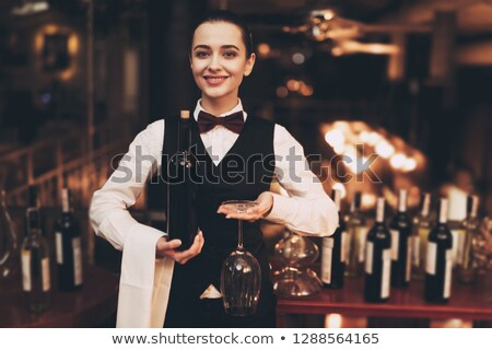 Young elegant sommelier tasting red wine from one of glasses Stock photo © pressmaster