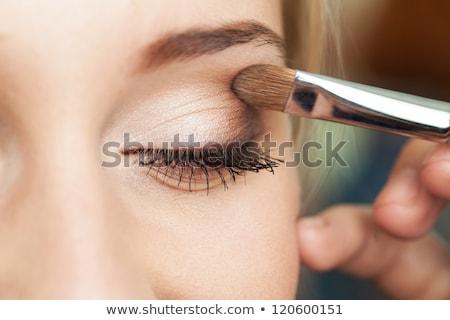 Beautiful model applying eyeliner close-up on eye Stock photo © serdechny