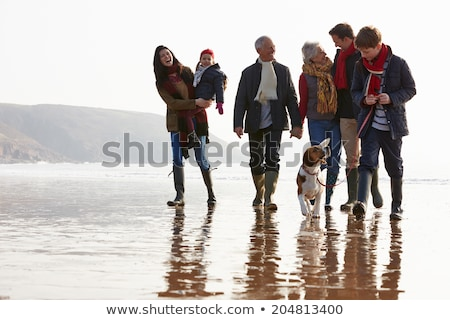 happy family walking with beagle dog on beach stock photo © dolgachov