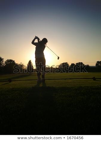 Female golf player walking on fairway at dusk. Stock photo © lichtmeister