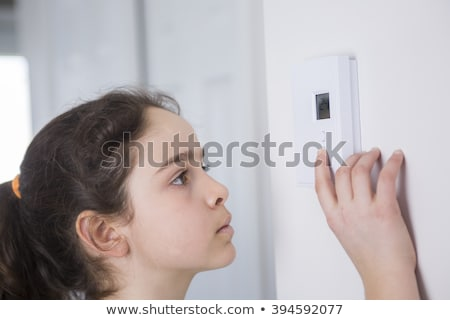 Teen Adjusting Thermostat On Central Heating Control Stock photo © Lopolo