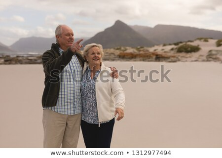 Happy active senior couple stading  on the beach pointing to something with his finger with mountain Stock photo © wavebreak_media