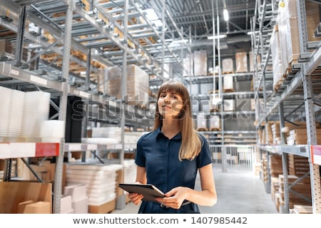 Pretty warehouse manager checking the inventory stock photo © Lopolo