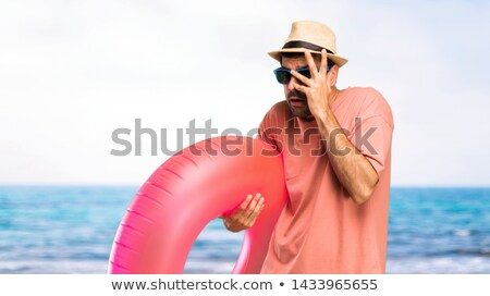 surprised man in sunglasses over tropical beach Stock photo © dolgachov