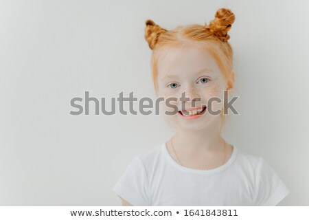 Positive attractive little girl with double ginger buns, freckles on face, toothy smile, dressed in  Stock photo © vkstudio