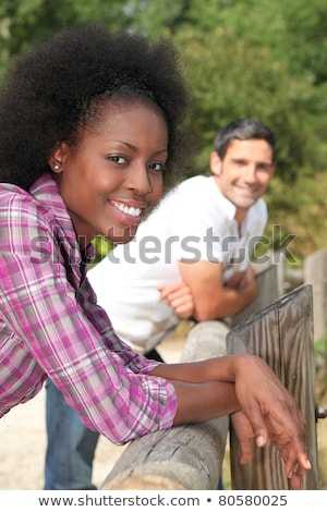 a black woman and a man leaning against wooden barrier Stock photo © photography33