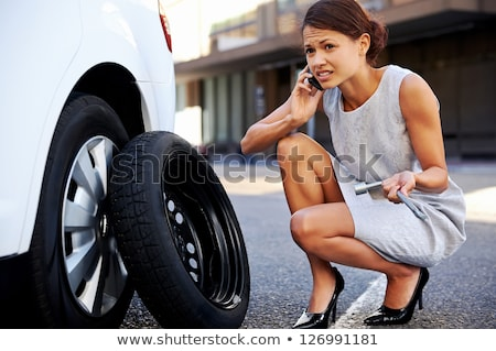 Young woman and the car with deflated wheel  Stock photo © Nobilior