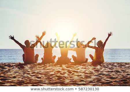 group of friends sitting on beach together stock photo © monkey_business