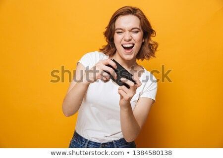 Girl playing with smartphone in hands Stock photo © LoopAll