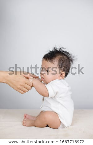 cute toddler baby sitting on moms hands stock photo © dariazu