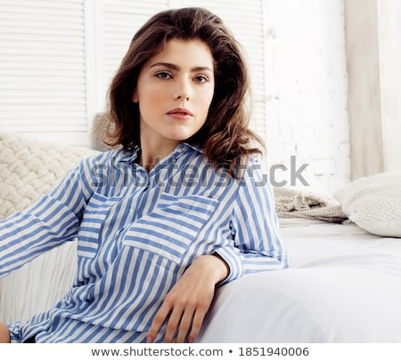young pretty brunette woman in her bedroom sitting at window happy smiling lifestyle people concept stock photo © iordani