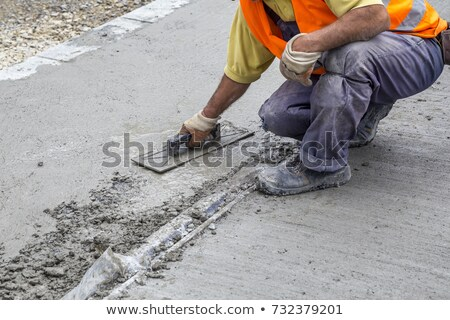 construction worker spreading wet concrete stock photo © zurijeta