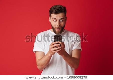Guapo joven teléfono móvil mirando foto Foto stock © deandrobot