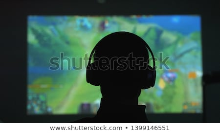 Hands of young gamer man playing video games on computer in dark Stock photo © deandrobot