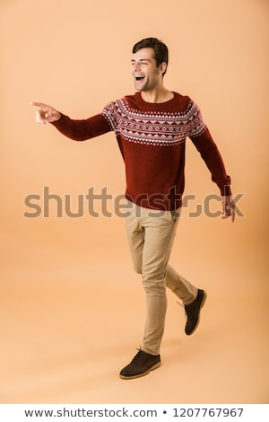 Full length image of unshaved man 20s with bristle wearing knitt Stock photo © deandrobot
