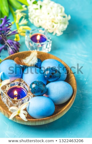 Easter eggs, candles and white hyacinth on a blue concrete Stock photo © artsvitlyna