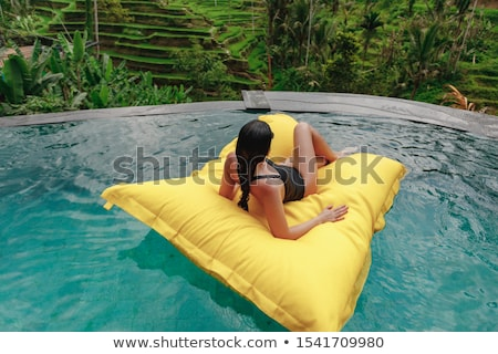 Stock photo: Enjoying suntan. Vacation concept. Top view of slim young woman in bikini on the blue air mattress i
