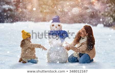 Family Sculpts Snowman from Snow in Winter Park Stock photo © robuart