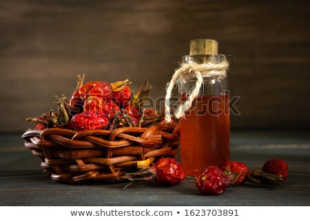 A bottle of rose hip seed oil with dried rose hips Stock photo © madeleine_steinbach
