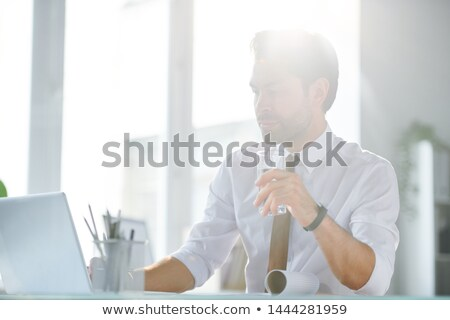 Young confident business analyst or broker with glass of water Stock photo © pressmaster