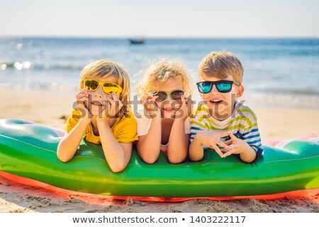 Children sit on an inflatable mattress in sunglasses against the sea and have fun Stock photo © galitskaya