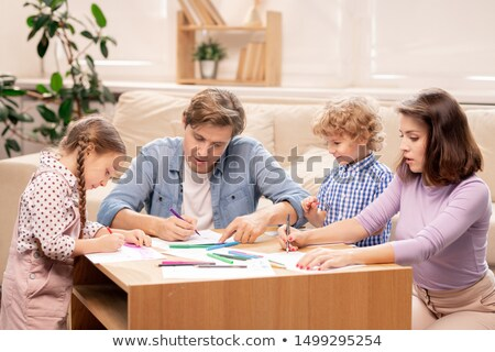 Young family of married couple and their two little elementary age kids drawing Stock photo © pressmaster