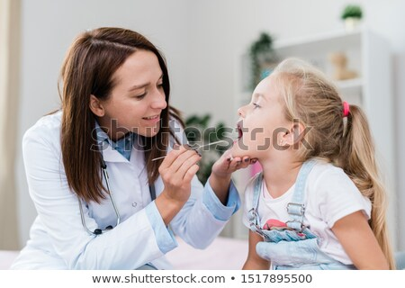 Sick little girl with open mouth while clinician examining her sore throat Stock photo © pressmaster