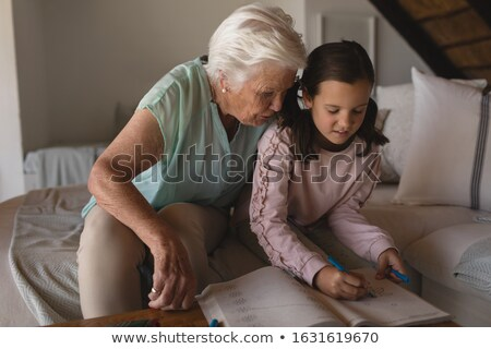 Foto stock: Front View Of A Grandmother Helping Her Granddaughter With Homework In Living Room At Home