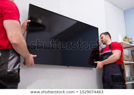 Mężczyzna LCD telewizji ściany Zdjęcia stock © AndreyPopov